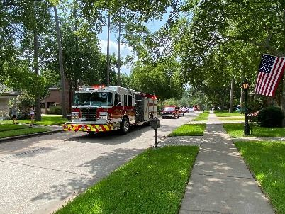 Fire truck leading parade through neighborhood.